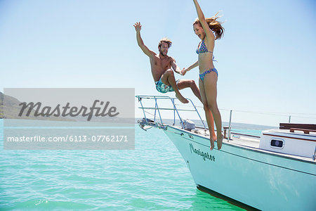 Couple jumping off boat together Stock Photo - Premium Royalty-Free, Image code: 6113-07762171