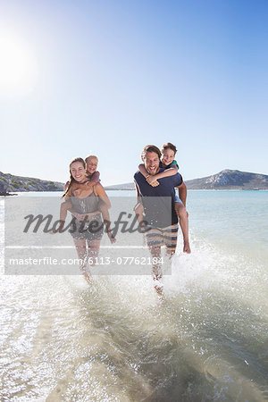 Family running in water on beach Stock Photo - Premium Royalty-Free, Image code: 6113-07762184