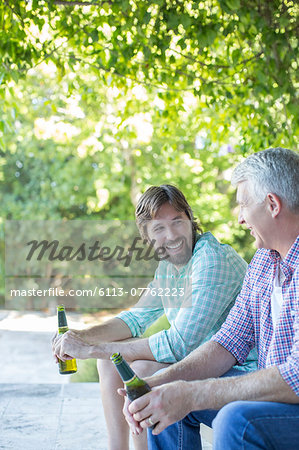 Father and son drinking outdoors Stock Photo - Premium Royalty-Free, Image code: 6113-07762223