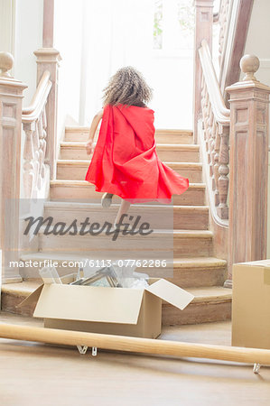 Young girl running up stairs playing Stock Photo - Premium Royalty-Free, Image code: 6113-07762286