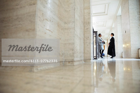 Lawyer and judge talking in hallway of courthouse Stock Photo - Premium Royalty-Free, Image code: 6113-07762335