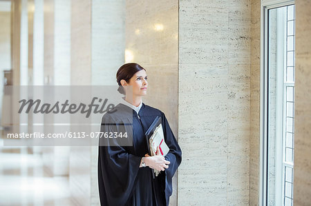 Judge looking out window in courthouse Stock Photo - Premium Royalty-Free, Image code: 6113-07762344
