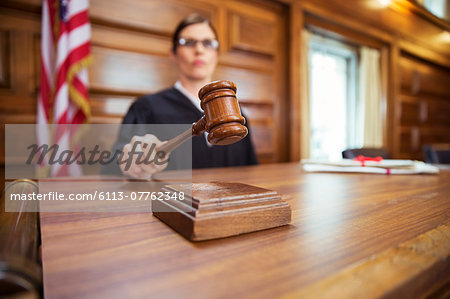 Judge banging gavel in court Stock Photo - Premium Royalty-Free, Image code: 6113-07762348