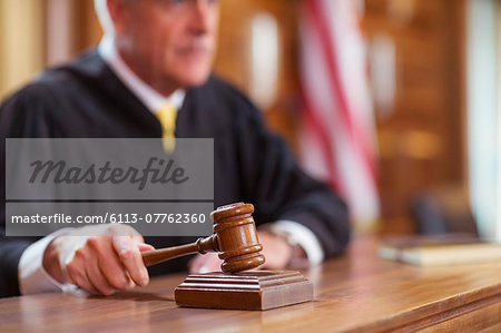 Judge banging gavel in court Stock Photo - Premium Royalty-Free, Image code: 6113-07762360