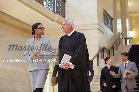 Judge and lawyer walking through courthouse together Stock Photo - Premium Royalty-Free, Image code: 6113-07762381