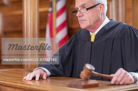 Judge banging gavel in court Stock Photo - Premium Royalty-Free, Image code: 6113-07762383