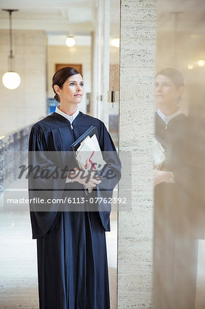 Judge looking out window in courthouse Stock Photo - Premium Royalty-Free, Image code: 6113-07762392