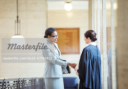 Judge and lawyer shaking hands in courthouse Stock Photo - Premium Royalty-Free, Image code: 6113-07762417