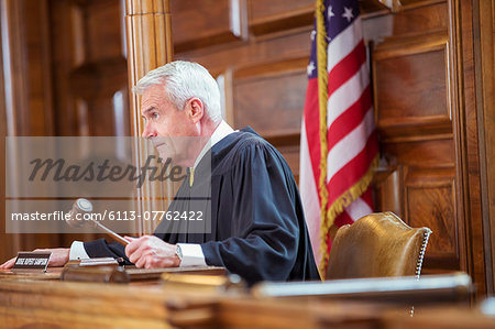 Judge banging gavel in court Stock Photo - Premium Royalty-Free, Image code: 6113-07762422