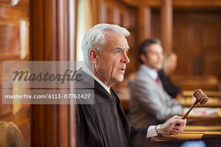Judge banging gavel in court Stock Photo - Premium Royalty-Free, Image code: 6113-07762427