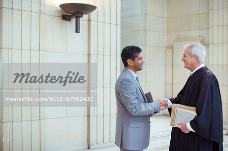Judge and lawyer shaking hands in courthouse Stock Photo - Premium Royalty-Free, Image code: 6113-07762430