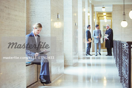 Lawyer working on digital tablet in courthouse Stock Photo - Premium Royalty-Free, Image code: 6113-07762433