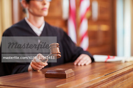 Judge banging gavel in court Stock Photo - Premium Royalty-Free, Image code: 6113-07762453