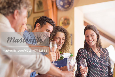 Man pouring drinks to family members Stock Photo - Premium Royalty-Free, Image code: 6113-07762566