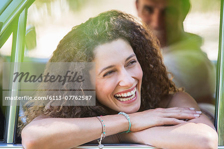 Woman relaxing on car door during car ride Stock Photo - Premium Royalty-Free, Image code: 6113-07762587