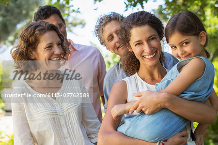 Mother carrying daughter in arms with family outdoors Stock Photo - Premium Royalty-Free, Image code: 6113-07762589