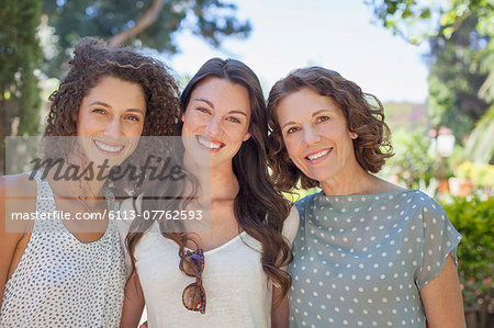 Mother and daughters hugging outdoors Stock Photo - Premium Royalty-Free, Image code: 6113-07762593