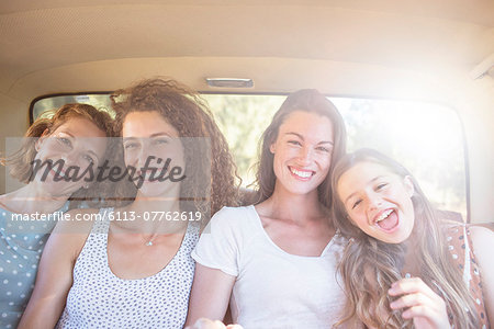 Four women sitting in backseat of car Stock Photo - Premium Royalty-Free, Image code: 6113-07762619