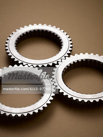 Close up of interlocking metal gears Stock Photo - Premium Royalty-Free, Image code: 6113-07790187
