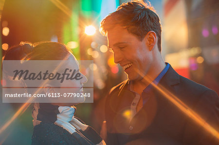Couple hugging on city street at night Stock Photo - Premium Royalty-Free, Image code: 6113-07790248