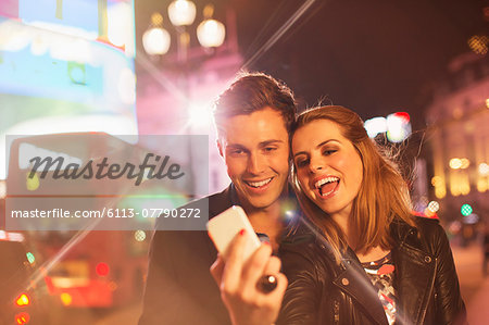 Couple taking cell phone picture together on city street at night Stock Photo - Premium Royalty-Free, Image code: 6113-07790272