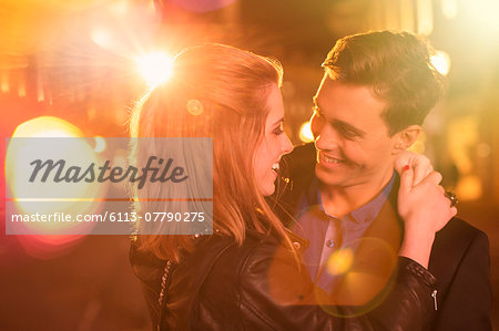 Couple hugging on city street at night Stock Photo - Premium Royalty-Free, Image code: 6113-07790275
