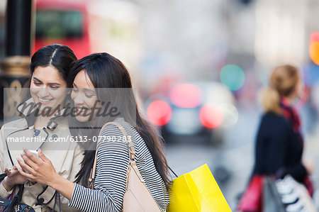 Women looking at cell phone on city street Stock Photo - Premium Royalty-Free, Image code: 6113-07790283