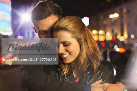 Couple hugging on city street at night Stock Photo - Premium Royalty-Free, Image code: 6113-07790298
