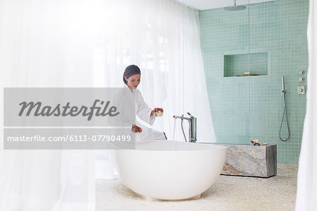 Woman running bath in modern bathroom Stock Photo - Premium Royalty-Free, Image code: 6113-07790499