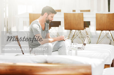 Man writing notes at laptop on sofa in modern living room Stock Photo - Premium Royalty-Free, Image code: 6113-07790547