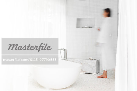 Blurred view of woman walking in modern bathroom Stock Photo - Premium Royalty-Free, Image code: 6113-07790555