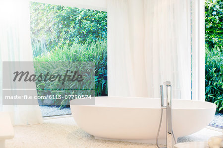 Bathtub, curtains, and windows in modern bathroom Stock Photo - Premium Royalty-Free, Image code: 6113-07790574