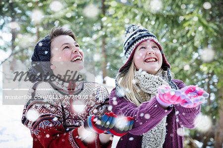 Siblings catching snow together Stock Photo - Premium Royalty-Free, Image code: 6113-07790600