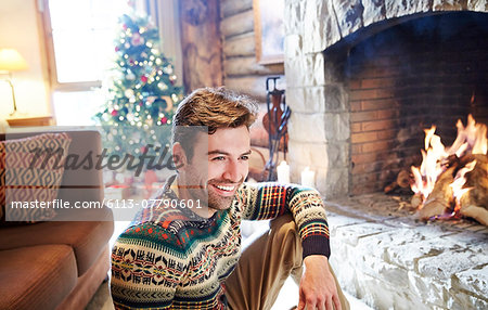 Man in warm sweater enjoying fireplace Stock Photo - Premium Royalty-Free, Image code: 6113-07790601
