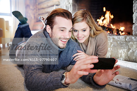 Couple looking at cell phone together Stock Photo - Premium Royalty-Free, Image code: 6113-07790607