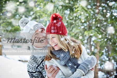 Couple playing in snow together Stock Photo - Premium Royalty-Free, Image code: 6113-07790620