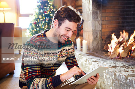 Man using digital tablet in front of fireplace Stock Photo - Premium Royalty-Free, Image code: 6113-07790665
