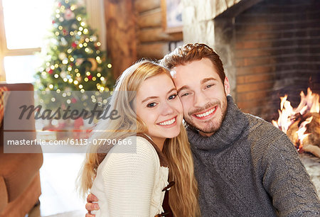 Couple hugging in front of fireplace Stock Photo - Premium Royalty-Free, Image code: 6113-07790666