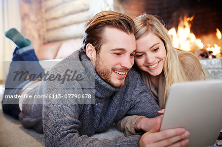 Couple using digital tablet by fireplace together Stock Photo - Premium Royalty-Free, Image code: 6113-07790678