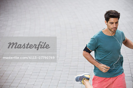 Man running through city streets Stock Photo - Premium Royalty-Free, Image code: 6113-07790749