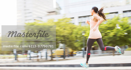 Woman running through city streets Stock Photo - Premium Royalty-Free, Image code: 6113-07790781