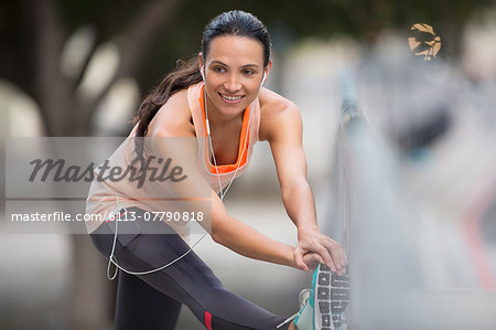 Woman stretching before exercising on city street Stock Photo - Premium Royalty-Free, Image code: 6113-07790818