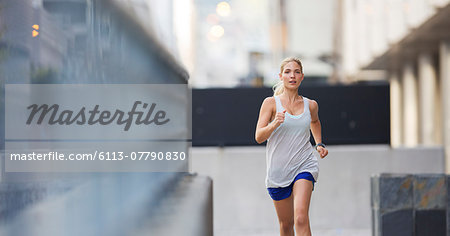 Woman running through city streets Stock Photo - Premium Royalty-Free, Image code: 6113-07790830