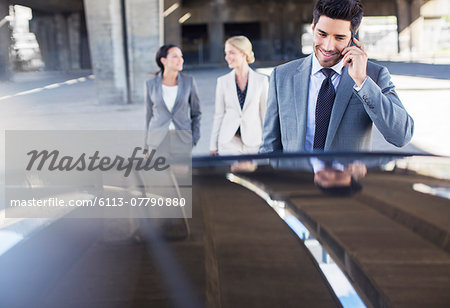Business people walking towards car in parking garage Stock Photo - Premium Royalty-Free, Image code: 6113-07790880