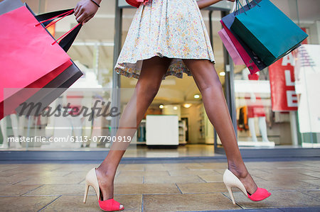 Woman carrying shopping bags in shopping mall Stock Photo - Premium Royalty-Free, Image code: 6113-07790919