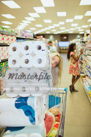 Woman pushing full shopping cart in grocery store Stock Photo - Premium Royalty-Free, Image code: 6113-07790920