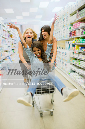 Women playing with shopping cart in grocery store Stock Photo - Premium Royalty-Free, Image code: 6113-07790933