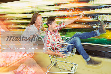 Blurred view of couple playing with shopping cart in grocery store Stock Photo - Premium Royalty-Free, Image code: 6113-07790934