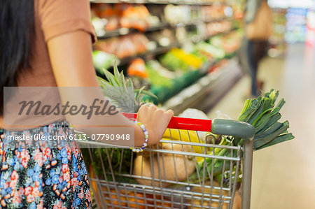 Close up of woman pushing full shopping cart in grocery store Stock Photo - Premium Royalty-Free, Image code: 6113-07790948