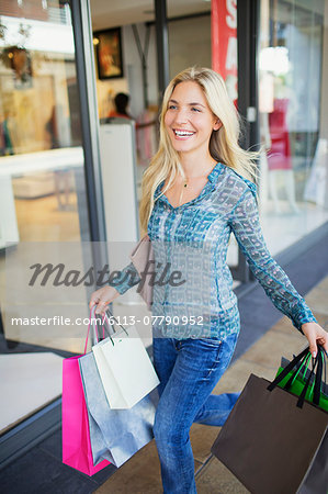 Woman carrying shopping bags in shopping mall Stock Photo - Premium Royalty-Free, Image code: 6113-07790952